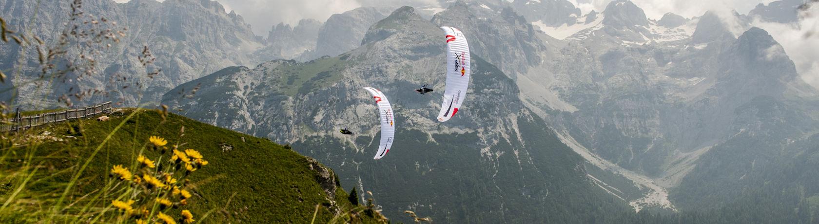 2 X-Alps Piloten im Wingover, Hintergrund Berge